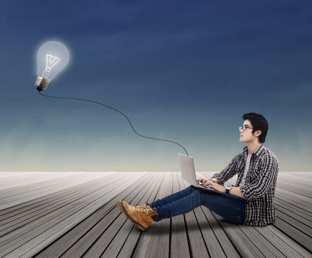 indian student: Portrait of college student looking at lit bulb with laptop outdoor
