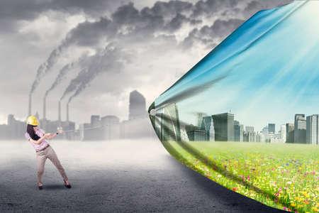 contaminacion del aire: Ingeniero de tratar de salvar el medio ambiente tirando de una bandera de la nueva ciudad verde