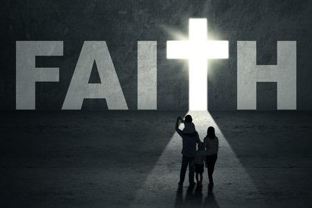 el cielo: Vista posterior de la joven familia cristiana a caminar hacia la puerta fe