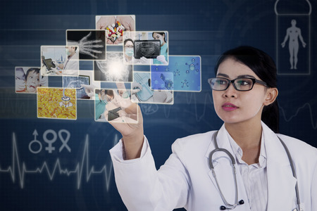 Young asian female doctor touching photos on touchscreen monitor button photo