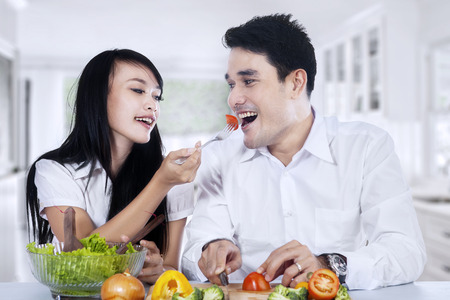 Happy couple preparing vegetable salad in their kitchen at home photo