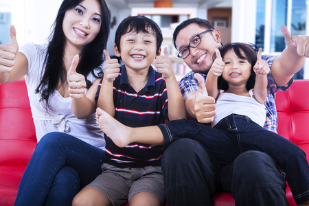 Portrait of happy asian family sitting on couch and showing thumbs up  Shot at home photo
