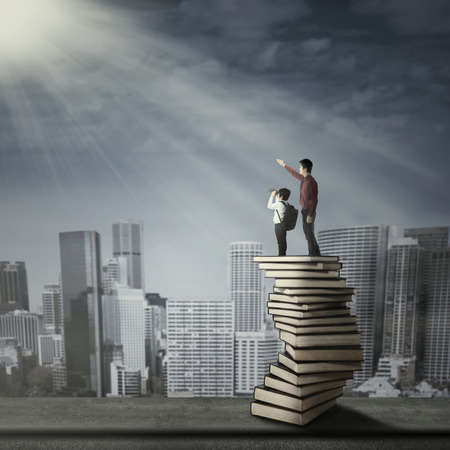 Businessman with little child standing on a stack of books Stock Photo