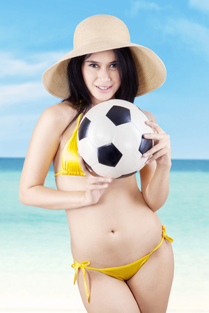 Portrait of sexy model wearing bikini with a soccer ball. shoot at the beach photo