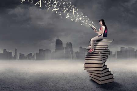 libros volando: Estudiante universitaria estudiando mientras está sentado en una pila de libros