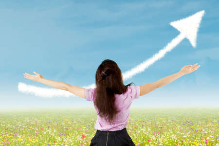 enhance: Businesswoman raising her arms with up arrow sign as background