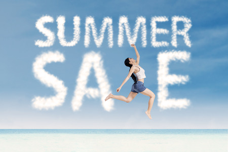 Attractive woman jumping make the word summer sale photo
