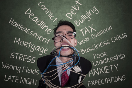Stressed businessman tied with a rope at classroom photo