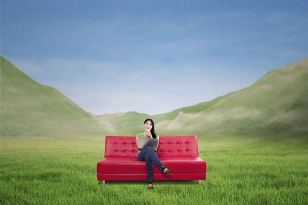 Beautiful woman having coffee on red sofa with laptop outdoor photo