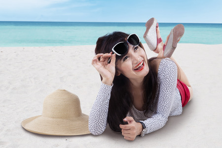 chinese hat: Beautiful asian girl lying on the beach to enjoy summertime Stock Photo