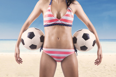 Beautiful body of female soccer fan wearing bikini while holding soccer balls at beach photo