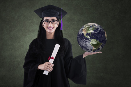 Beautiful female graduate holding earth and certificate in class photo