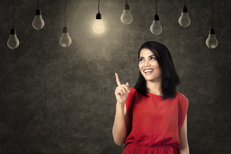 Smiling woman pointing at bright lamp photo