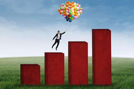 Young businesswoman flying with balloons over upward business chart photo