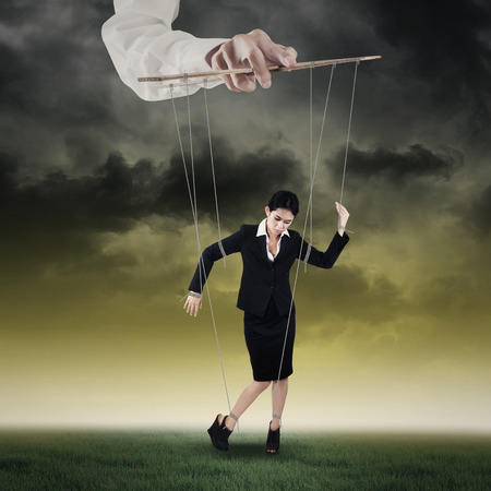 Businesswoman hanging on string and controlled by a hand Stock Photo