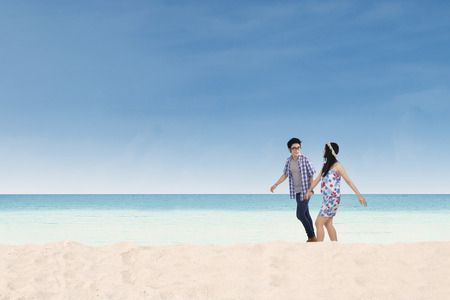 Romantic young couple walking together on the beach while holding hands photo