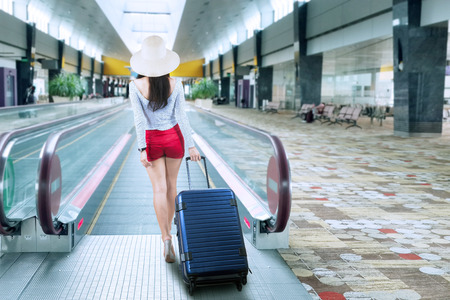 arrive: Young woman with a suitcase walking to escalator at airport Stock Photo