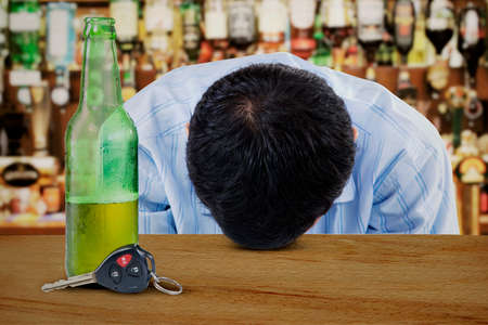 beer and wine: Alcoholic young man sleeping on the table with car keys Stock Photo