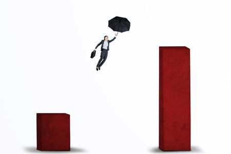 financial obstacle: Young businesswoman flying with umbrella over upward business chart to higher chart