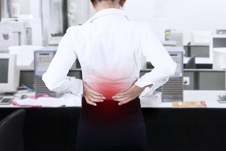 Young businesswoman having back pain while working at office  Imagens