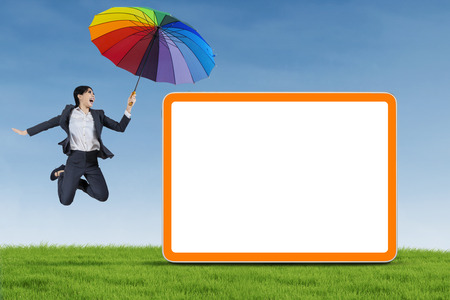 Excited businesswoman holding umbrella and jumping with blank board on the meadow photo