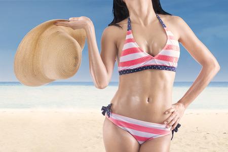 Closeup of beautiful woman body holding a straw hat at beach photo