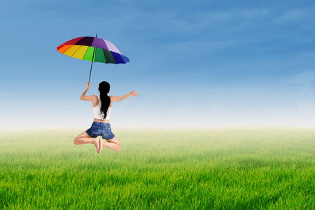 Happy girl jumping with a rainbow umbrella at green meadow photo