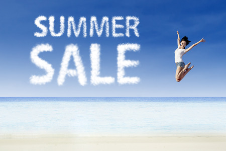 summer sale: Woman jumping for summer sale at beach