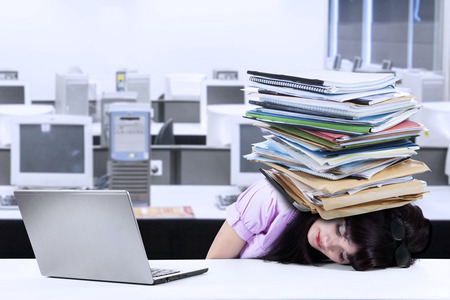 Depressed young businesswoman with a pile of documents on her head at office photo