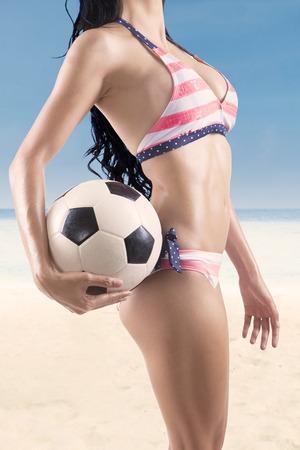 Sexy woman in bikini holding soccer ball. Shoot outdoors photo