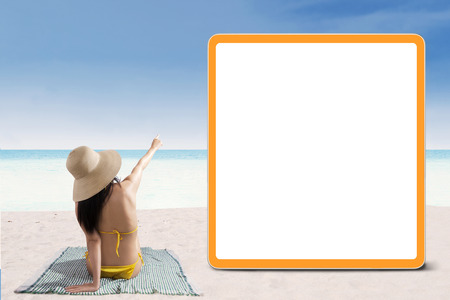Portrait of sexy woman in bikini pointing at copyspace photo
