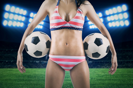 Sexy woman wearing swimsuit holding soccer balls at field photo