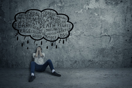 若い男の問題を取得、座っていると恐怖で壁に傾いています。 写真素材