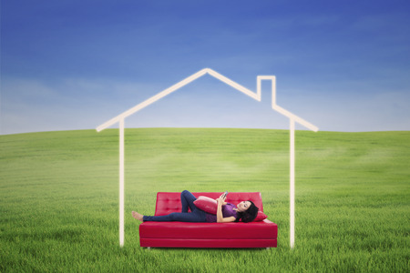 Asian female is lying down on sofa using touchpad outdoor with dream house picture photo