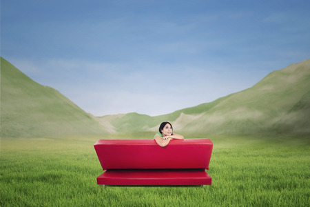 Picture from behind red sofa with pensive woman on mountain landscape photo