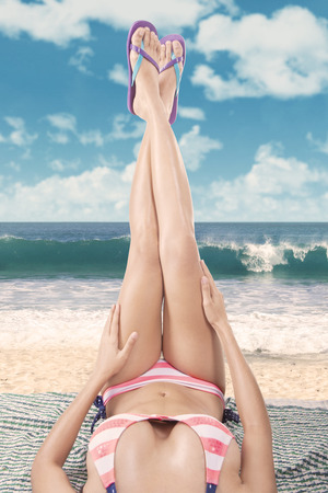 Beautiful woman legs in sandals up in the air. Shoot at beach on summertime photo