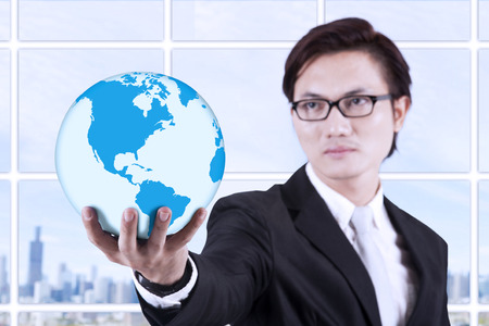 environmental suit: Asian businessman looking smart with glasses holding a globe