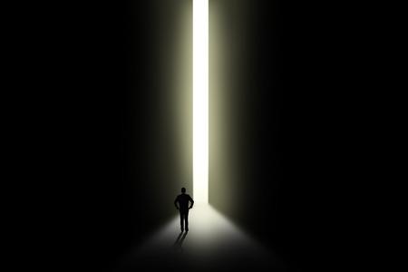 open doorway: Silhouette of businessman looking at bright light in doorway