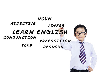 idiomas: Estudiante de escuela primaria escribe materiales en idioma Ingl�s en la pizarra