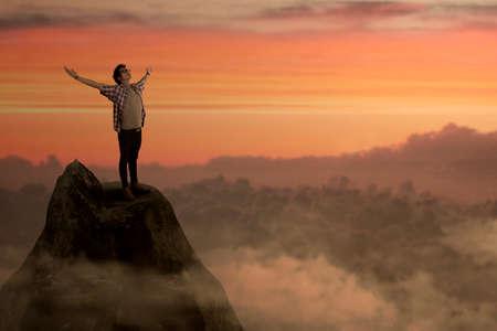Success man on mountain peak enjoying freedom photo