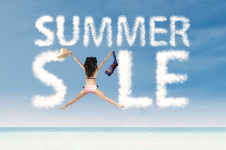 woman holding bag: Summer sale clouds with jumping woman holding bag and hat at beach Stock Photo