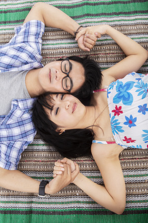 Romantic young asian couple lying on picnic blanket photo