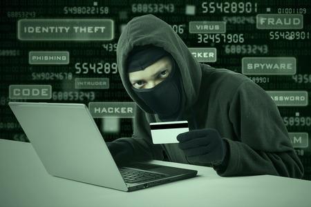 Internet Diefstal - een man met een bivakmuts en met een creditcard, terwijl zat achter een laptop,