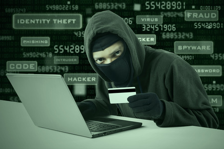 Internet Theft - a man wearing a balaclava and holding a credit card while sat behind a laptop,  photo