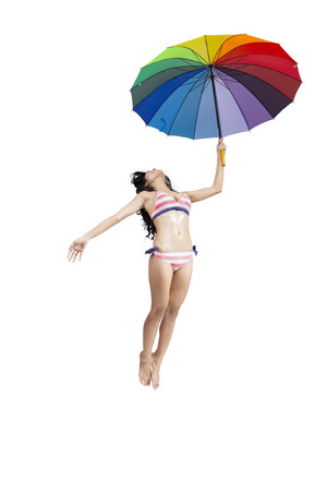 Happy woman wearing bikini jumping with rainbow umbrella isolated on white background photo