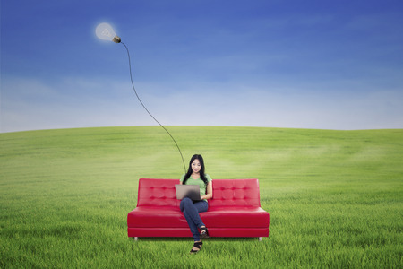 Young female is typing on laptop sitting on red sofa under lamp outdoor  photo