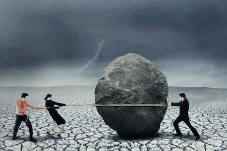 savings problems: Portrait of young business teamwork try to move the big stone as a big obstacle