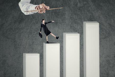 marioneta: Empresaria atada con cuerdas controladas por titiritero caminar sobre gráfico