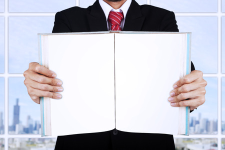 Unrecognised businessman is holding a blank open book at office