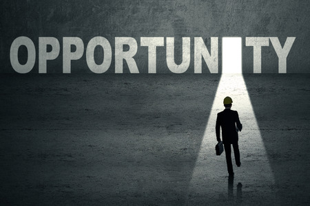 Young businessman walking toward an opportunity door photo